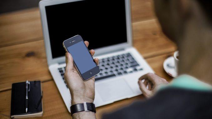 Mand med mobil og laptop