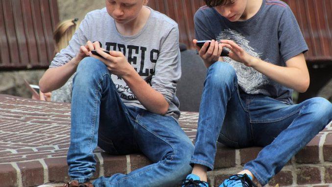 2 drenge der spiller på mobiltelefoner